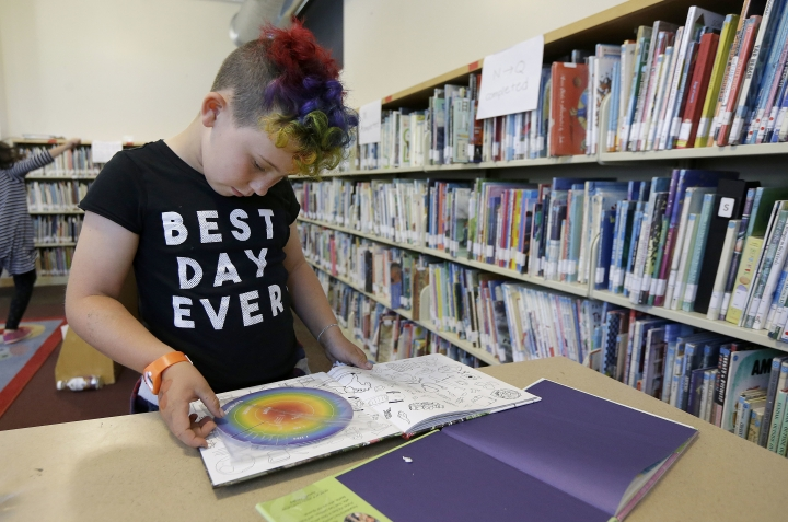 "In this Wednesday, July 12, 2017 photo, Sam, 9, reads a book in the library at Bay Area Rainbow Day Camp in El Cerrito, Calif. The camp caters to transgender and ""gender fluid"" children, aged 4-12, making it one of the only camps of its kind in the world open to preschoolers, experts say. (AP Photo/Jeff Chiu)"