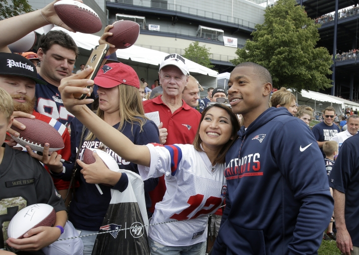 Boston Celtics basketball player Isaiah Thomas, right, stands with a fan for a selfie following an NFL football joint practice with the Jacksonville Jaguars and the New England Patriots, Monday, Aug. 7, 2017, in Foxborough, Mass. (AP Photo/Steven Senne)