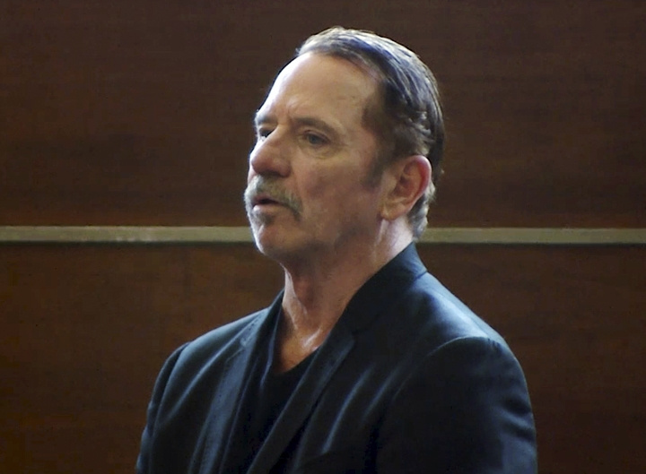 """In this still image from video, actor Tom Wopat stands during arraignment Thursday, Aug. 3, 2017, in Waltham, Mass., on indecent assault and battery and drug possession charges. Wopat who played Luke Duke on the 1980s television show """"The Dukes of Hazzard"""" pleaded not guilty to the charges. Wopat, 65, was arrested on Wednesday night as he was leaving rehearsal for a performance of """"42nd Street."""" (WCVB-TV via AP, Pool)"""