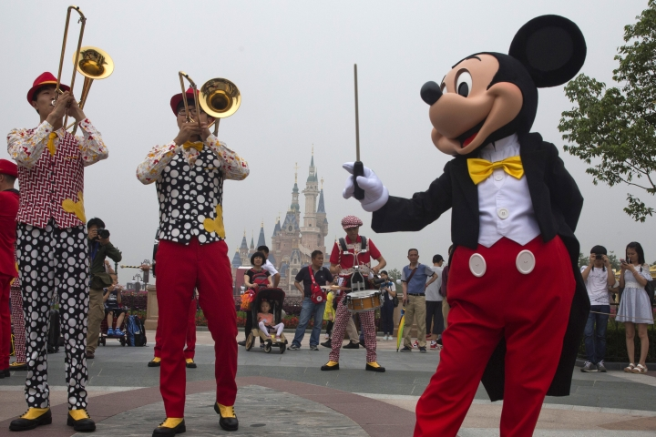 FILE - In this Thursday, June 16, 2016, file photo, Mickey Mouse entertains visitors on the opening day of the Disney Resort in Shanghai, China. The Walt Disney Co. reports earnings, Tuesday, Aug. 8, 2017. (AP Photo/Ng Han Guan, File)