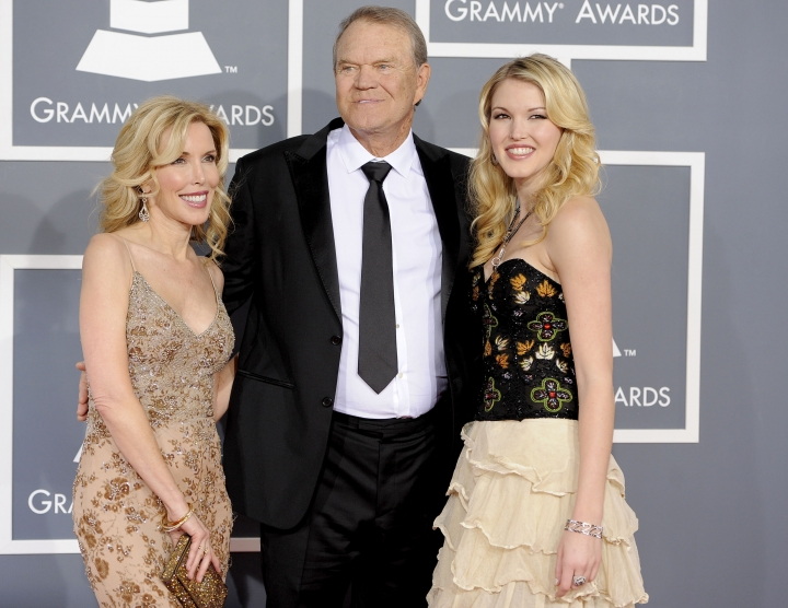 """FILE - In this Feb. 12, 2012 file photo, Glen Campbell, center, Kim Woolen, left, and Ashley Campbell arrive at the 54th annual Grammy Awards in Los Angeles. Campbell, the grinning, high-pitched entertainer who had such hits as """"Rhinestone Cowboy"""" and spanned country, pop, television and movies, died Tuesday, Aug. 8, 2017. He was 81. Campbell announced in June 2011 that he had been diagnosed with Alzheimer's disease. (AP Photo/Chris Pizzello, File)"""
