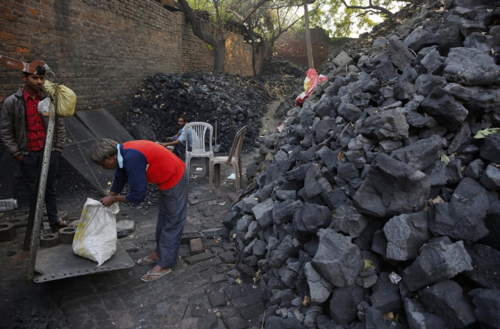 FILE - In this Dec. 3, 2015 file photo, an Indian coal vendor weighs coal for a customer in Lucknow, India. Within the wild energy market of the world's second-most populous nation, predictions are proving tricky. India had been projected to become a carbon-belching behemoth, fueled by thermal power plants demanding ever more coal for decades to come. Now, some analysts are saying that may not happen. (AP Photo/Rajesh Kumar Singh, File)