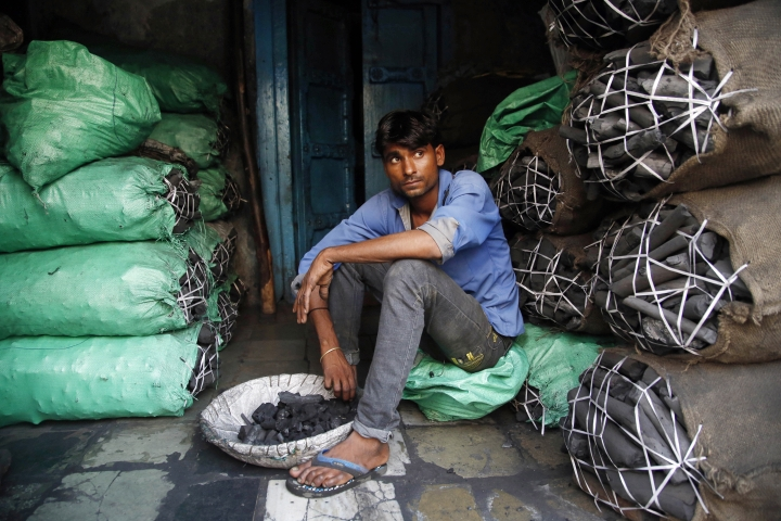 FILE- In this Dec. 3, 2015 file photo, a worker at a retail coal store awaits customers in Mumbai, India. India is the world's third-largest carbon emitter among nations, and relies on coal-fired power plants to produce most of its energy. With a population of 1.3 billion and a fast-industrializing economy, those energy needs had been forecast to soar. So signs that the country's appetite for burning more coal may be close to sated would be welcome news, given fears of a looming escalation in climate-warming carbon emissions. (AP Photo/Rajanish Kakade, File)