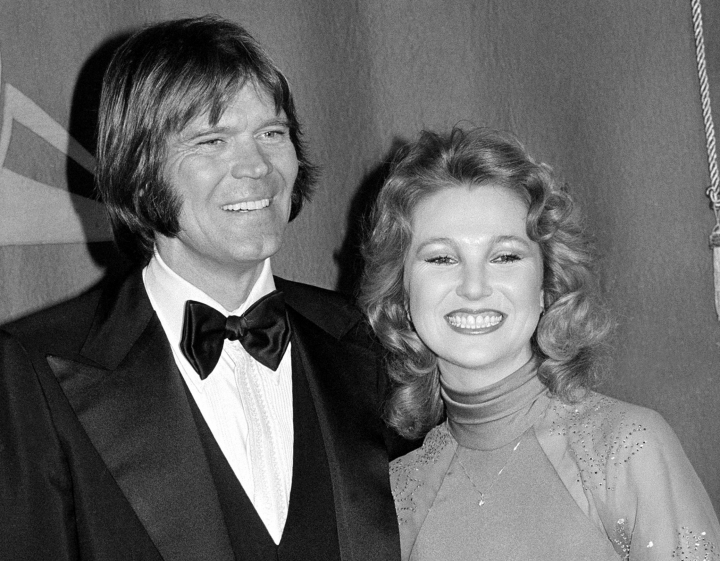 "FILE - In this Feb. 15, 1979 file photo, country singers Glen Campbell, left, and Tanya Tucker, engaged to one another, are shown at the Grammy Awards in Los Angeles. Campbell, the grinning, high-pitched entertainer who had such hits as ""Rhinestone Cowboy"" and spanned country, pop, television and movies, died Tuesday, Aug. 8, 2017. He was 81. Campbell announced in June 2011 that he had been diagnosed with Alzheimer's disease. (AP Photo, File)"