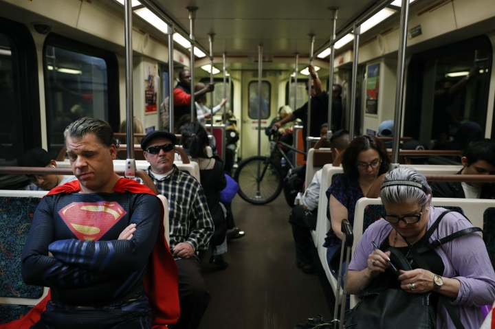 "In this Tuesday, May 16, 2017 photo, superhero impersonator Justin Harrison, left, rides a Metro train wearing a Superman costume on his way to Hollywood Boulevard in Los Angeles. ""I always go out in a costume,"" said Harrison. ""I love seeing people happy and seeing them smile."" (AP Photo/Jae C. Hong)"