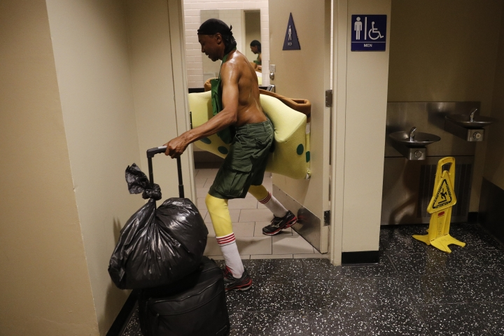"""In this Monday, April 17, 2017 photo, covered in sweat, impersonator Belnarr Golden enters a public restroom with his SpongeBob SquarePants costume folded in half after working on Hollywood Boulevard in Los Angeles. While the Hollywood we see in movies is a place of glamour and beautiful celebrities, the cast of superheroes filling Hollywood Boulevard is frequently anything but. Many are people struggling to make a buck as they pursue their dream of stardom. """"I crack jokes on them. That's my trick. I make them laugh,"""" said Golden. """"If I stand still, I'm not getting paid."""" (AP Photo/Jae C. Hong)"""