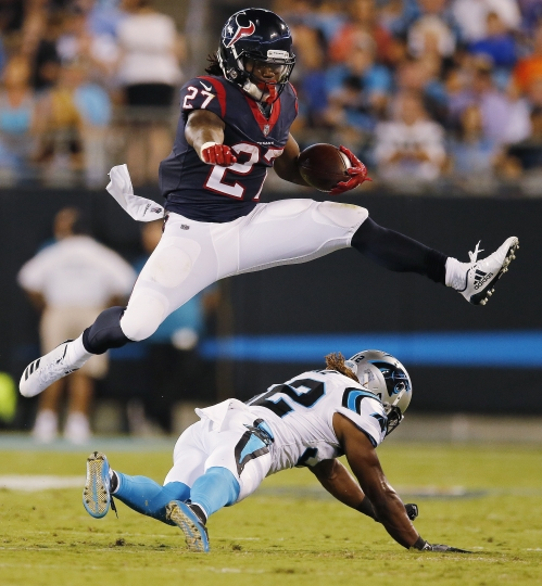 Houston Texans running back D'Onta Foreman (27) leaps over Carolina Panthers cornerback Cole Luke (32) during the first half of an NFL preseason football game, Wednesday, Aug. 9, 2017, in Charlotte, N.C. (AP Photo/Jason E. Miczek)