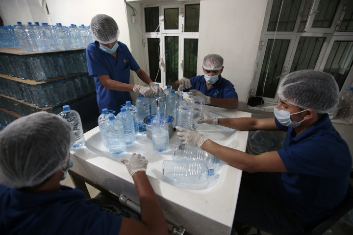 In this photo taken on Saturday, Jul. 8, 2017, workers fill bottles with water at the mineral water refilling station in Sanaa, Yemen. Yemen's raging two-year conflict has served as an incubator for lethal cholera. (AP Photo/Hani Mohammed)