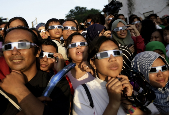 FILE - In this Wednesday, March 9, 2016 file photo, people wearing protective glasses look up at the sun to watch a solar eclipse in Jakarta, Indonesia. Doctors say not to look at the sun without eclipse glasses or other certified filters except during the two minutes or so when the moon completely blots out the sun, called totality. That's the only time it's safe to view the eclipse without protection. When totality is ending, then it's time to put them back on. (AP Photo/Dita Alangkara)