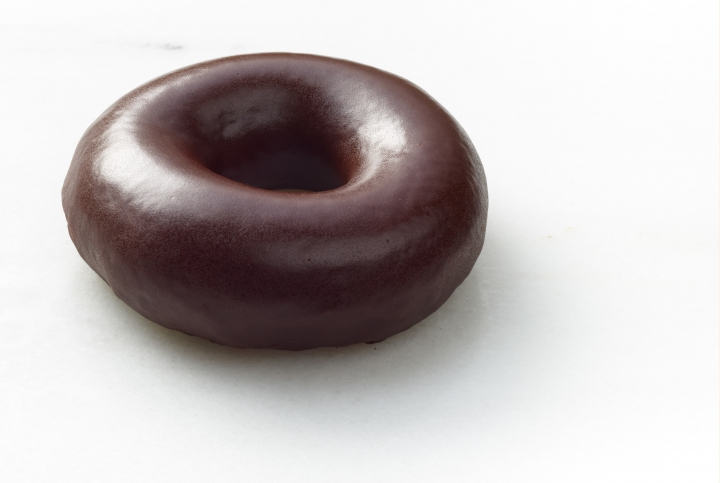 This undated product image provided by Krispy Kreme shows its signature glazed doughnut with a chocolate sheen. The doughnut chain is introducing the treat in honor of the Aug. 21, 2017, solar eclipse, where the moon will pass in front of the sun. The doughnuts will be available in participating stores on Aug. 21 as well as during limited hours on Aug. 19 and Aug. 20. (Krispy Kreme via AP)