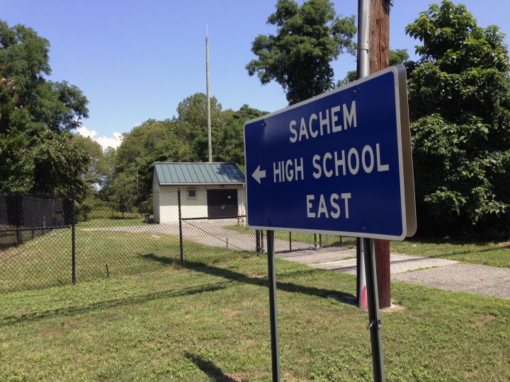 A sign points to Sachem East High School in Farmingville, N.Y. where police say log fell on a teenage football player's head, killing him, Thursday Aug. 10, 2017. Joshua Mileto, 16, was participating in a pre-season drill with a group of high school football players, carrying a large log overhead for a workout, when the wood fell on his head. The 11th-grader was taken from the school to Stony Brook University Hospital, where he was pronounced dead. (AP Photo/Frank Eltman)