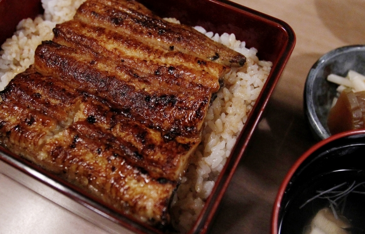 "In this Aug. 2, 2017 photo, unajyu is served at Hashimoto, a Michelin one-star unagi restaurant in Tokyo. Known as ""unajyu,"" the grilled ""kabayaki"" eel delicacy served on hot steaming rice in a neat lacquer box is what many Japanese people indulge in during the summer to celebrate the Day of the Ox. The endangered Japanese summer delicacy may get a new lease on life with commercial farming. (AP Photo/Sherry Zheng)"