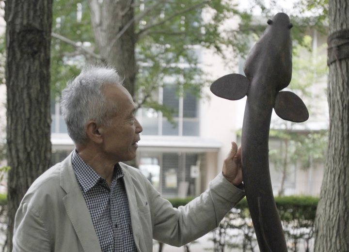 """In this July 27, 2017 photo, Katsumi Tsukamoto, self-proclaimed """"Dr. Eel"""" poses beside an eel statue on the Shonan campus of Nihon University, south of Tokyo. A professor at the only """"Eel Science Laboratory"""" in Japan, Tsukamoto believes that complete farming of Japanese eels will be a commercially viable possibility after only a decade. The endangered Japanese summer delicacy may get a new lease on life with commercial farming. (AP Photo/Sherry Zheng)"""