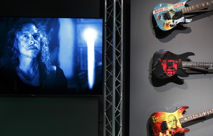 In this Wednesday, Aug. 9, 2017 photo, Metallica guitarist Kirk Hammett appears in a recorded video beside three of his guitars at the Peabody Essex Museum in Salem, Mass. A new exhibition opening Saturday, Aug. 12 at the museum features 135 works from Metallica guitarist Hammett's collection of classic horror and sci-fi movie posters and memorabilia, including some he says have inspired his music. (AP Photo/Michael Dwyer)