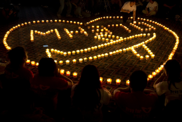 FILE - In this April 8, 2014, file photo, relatives of Chinese passengers onboard Malaysia Airlines Flight 370 hold a candlelight vigil for their loved ones in Beijing. U.S. seabed exploration company Ocean Infinity said on Friday, Aug. 11, 2017, it had offered to take the financial risk of a renewed search for the missing Malaysian airliner, as victims' families urged the Malaysian government to agree to a private-sector hunt for Flight 370's wreckage. (AP Photo/Andy Wong, File)