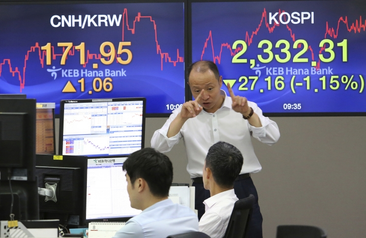 A currency trader gestures at the foreign exchange dealing room of the KEB Hana Bank headquarters in Seoul, South Korea, Friday, Aug. 11, 2017. Asian stock markets slumped on Friday following overnight losses on Wall Street as U.S. President Donald Trump's bellicose remarks prompted investors to unload shares in companies that have been on the rise in recent months. (AP Photo/Ahn Young-joon)
