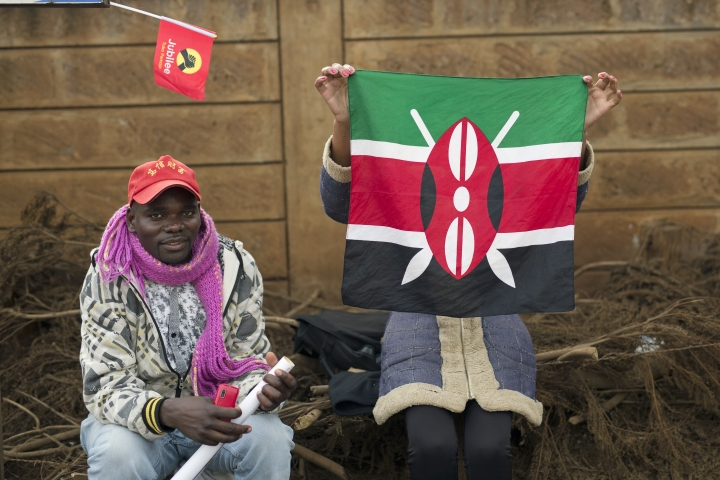 A supporter of President Uluru Kenyatta holds up a Kenyan flag in Kikuyu town, Kenya, in anticipation of the announcement of the presidential election's final results Friday, Aug. 11, 2017. The election commission urged Kenyans to be patient as they await the official results of Tuesday's disputed election, though the counting process has been repeatedly delayed.(AP Photo/Jerome Delay)