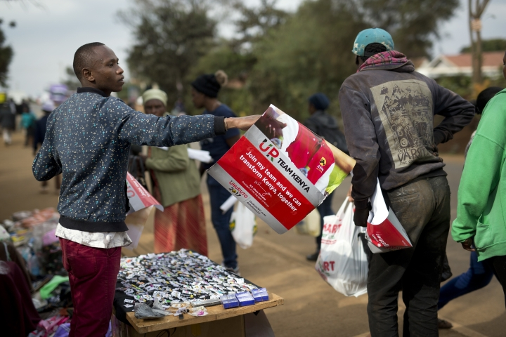 A supporter of President Uluru Kenyatta hands out posters in Kikuyu town, Kenya, in anticipation of the announcement of the presidential election's final results Friday, Aug. 11, 2017. The election commission urged Kenyans to be patient as they await the official results of Tuesday's disputed election, though the counting process has been repeatedly delayed. (AP Photo/Jerome Delay)