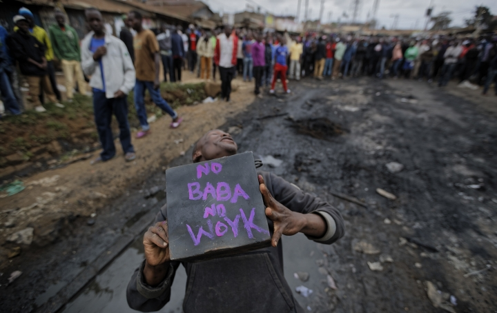 """A supporter of opposition leader Raila Odinga holds a metal box on which """"No Baba, No Work"""" is written, referring to Odinga, during demonstrations in the Kawangware slum of Nairobi, Kenya Thursday, Aug. 10, 2017. International observers on Thursday urged Kenyans to be patient as they awaited final election results following opposition allegations of vote-rigging, but clashes between police and protesters again erupted in Nairobi. (AP Photo/Ben Curtis)"""