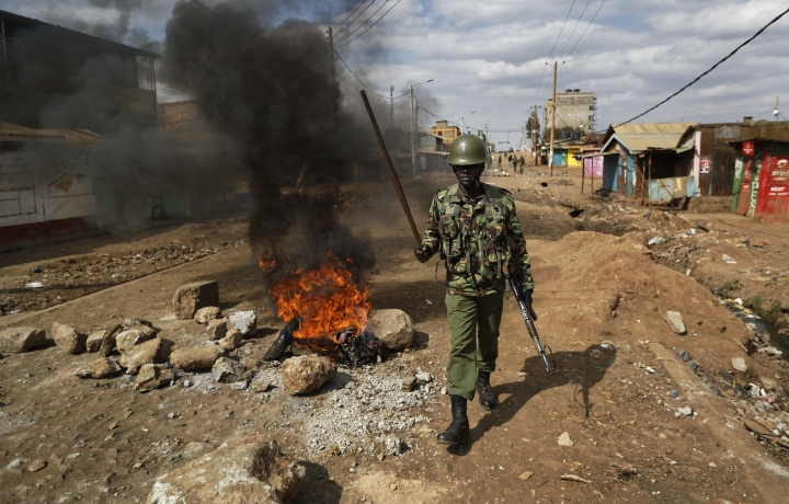 A riot policeman walks past burning barricades erected by protesters throwing rocks, during clashes in the Kawangware slum of Nairobi, Kenya Thursday, Aug. 10, 2017. International observers on Thursday urged Kenyans to be patient as they awaited final election results following opposition allegations of vote-rigging, but clashes between police and protesters again erupted in Nairobi. (AP Photo/Ben Curtis)