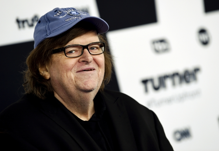 "FILE - In this May 17, 2017 file photo, filmmaker Michael Moore attends the Turner Network 2017 Upfront presentation at The Theater at Madison Square Garden in New York. Moore showed his patriotism by marching down the Avenue of the Americas with a drum and fife corps after making his Broadway debut. ""I say this to the people who disagree with me, we're all Americans. We're all in the same boat, and we're going to sink or swim together. I prefer not to sink. So let's find a way, if we can, to work together to save this country,"" Moore said Thursday, Aug. 10. .(Photo by Evan Agostini/Invision/AP, File)"