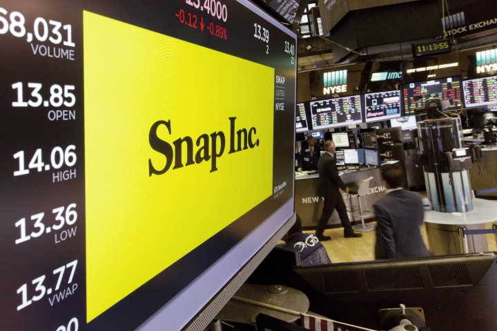 In this Monday, Aug. 7, 2017, photo, the Snap Inc. logo appears on a screen above a trading post on the floor of the New York Stock Exchange. Snap Inc. reports earnings, Thursday, Aug. 10, 2017. (AP Photo/Richard Drew)