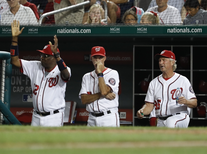 From left, Washington Nationals manager Dusty Baker (12), pitching coach Mike Maddux (51), and bench coach Chris Speier (35) react to loosing a challenge in the seventh inning of baseball game against the Miami Marlins, Tuesday, Aug. 8, 2017, in Washington. The Marlins won 7-3. (AP Photo/Carolyn Kaster)