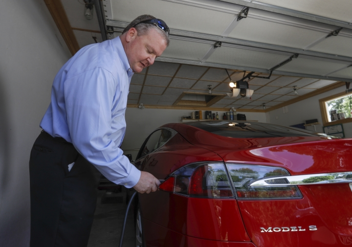 In this Thursday, July 13, 2017, photo, Jeff Solie plugs in his electric Tesla sedan at his home, in New Berlin, Wis. Electric cars are seeing growing support around the world. But there's a problem: There aren't enough places to plug those cars in. The nearest fast-charging Tesla Superchargers are 45 miles (72 kilometers) away. There are some public charging stations in nearby Milwaukee, at hotels and shopping centers, but Solie relies almost entirely on the charging system he set up in his garage. (AP Photo/Morry Gash)