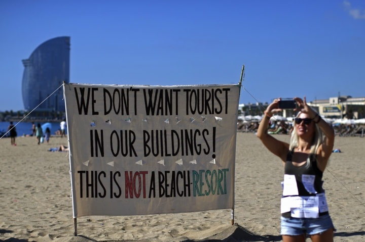"""A woman takes a picture during a protest against tourism in Barcelona, Spain, Saturday, Aug. 12, 2017. The residents claim that the influx of tourists has increased the price of rents and produced a spike in rowdy behavior by party-seeking foreigners. The protest comes amid growing tension between governmental authorities and radical leftist groups after they launched a campaign of vandalism against mass tourism in Barcelona and other parts of Spain. The banner reads in Catalan: """"For the abolition of tourist floors."""" (AP Photo/Manu Fernandez)"""