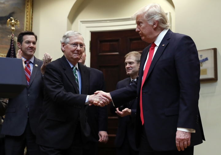 FILE - In this Feb. 16, 2017, file photo, President Donald Trump shakes hands with Senate Majority Leader Mitch McConnell of Ky., during a ceremony in the Roosevelt Room of the White House in Washington. Trump's attacks on McConnell come at the worst possible time, if the president's goal is actually to accomplish the agenda on health care, infrastructure and taxes he's goading his GOP ally to pass. Behind from left are Rep. Evan Jenkins, R-W.Va., and Rep. Jim Jordan, R-Ohio.(AP Photo/Carolyn Kaster, File)