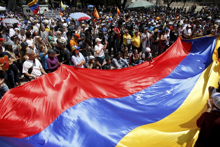 Anti-government demonstrators wave a Venezuelan flag during a protest against Venezuela's President Nicolas Maduro in Caracas, Venezuela, Saturday, Aug. 12, 2017. Opposition members called a demonstration to protest the seating of a special assembly to rewrite the constitution. Observers will be closely watching the turnout as the arrest of several mayors and the opposition's decision to compete in regional elections despite concerns the election for the constitutional assembly was marred by fraud. (AP Photo/Ariana Cubillos)