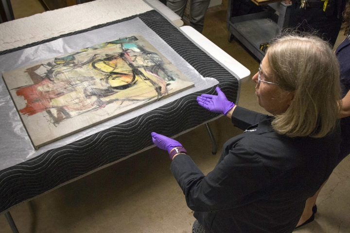 In this Aug. 9, 2017 photo provided by the University of Arizona, Dr. Nancy Odegaard, a conservator with the university, leads the authentication process for a recovered Willem de Kooning painting, in Phoenix. More than three decades after thieves made off with the valuable painting from the University of Arizona Museum of Art, officials have recovered the long sought piece from an antique dealer in New Mexico.(University of Arizona via AP)