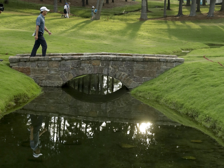 Kevin Kisner walks across the bridge on the 18th hole during the third round of the PGA Championship golf tournament at the Quail Hollow Club Saturday, Aug. 12, 2017, in Charlotte, N.C. (AP Photo/Chris O'Meara)