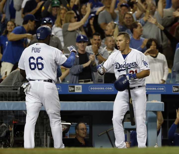 Los Angeles Dodgers' Yasiel Puig, left, gets congratulations from Joc Pederson, after Puig scored the third run on a single by Corey Seager against the San Diego Padres, during the sixth inning of a baseball game in Los Angeles, Saturday, Aug. 12, 2017. (AP Photo/Alex Gallardo)