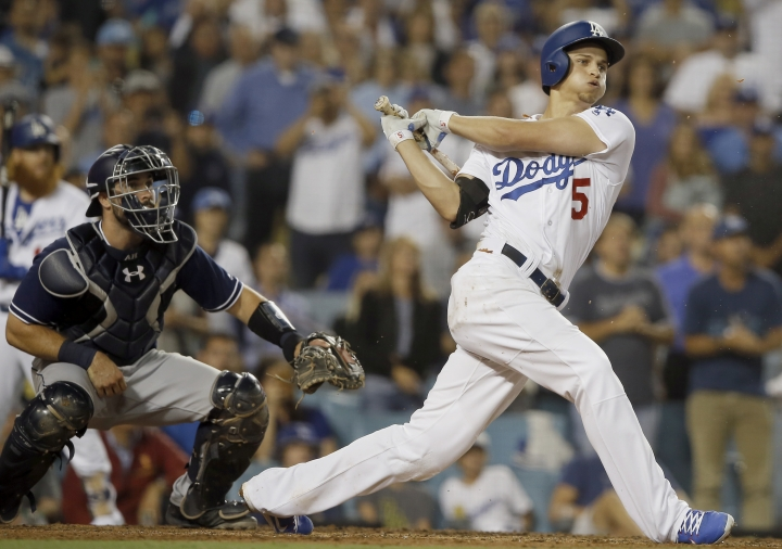 Los Angeles Dodgers' Corey Seager follows through on a three-run single in front of San Diego Padres catcher Austin Hedges during the sixth inning of a baseball game in Los Angeles, Saturday, Aug. 12, 2017. (AP Photo/Alex Gallardo)