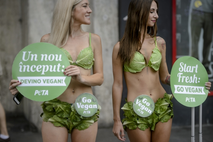 "The ""Lettuce Ladies"", a group of PETA activists, hold signs reading in Romanian and English 'start fresh: become vegan' during an event promoting a vegan lifestyle, downtown Bucharest, Romania, Monday, Aug. 14, 2017. Two PETA vegan ambassadors distributed vegan food to passers by in the Romanian capital, the latest stop in a tour including the United States, Russia and Turkey aimed at promoting a vegan lifestyle.(AP Photo/Andreea Alexandru)"