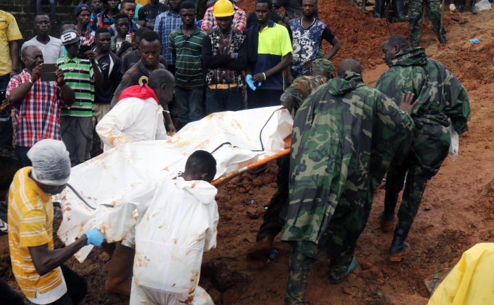 """In this photo taken on Monday, Aug. 14, 2017 and provided by IFRC, Red Cross volunteers remove bodies from the scene of heavy flooding and mudslides in Regent, just outside of Sierra Leone's capital Freetown. The Red Cross estimates that 600 people are still missing as the death toll from massive mudslides in Sierra Leone's capital is certain to rise. Authorities say more than 300 were killed in and around Freetown following heavy rains. Many victims were trapped under tons of mud as they slept. An official says the local mortuary is """"overwhelmed with corpses."""" (IFRC via AP)"""