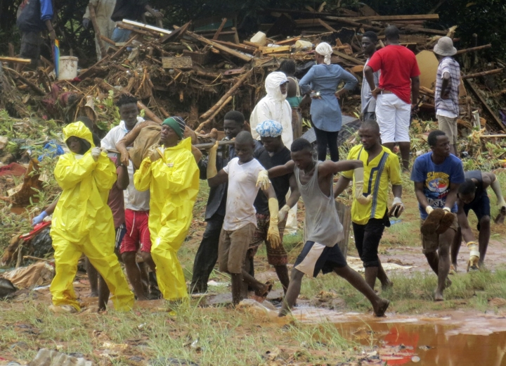 Rescue workers carry the body of a victim from the site of a mudslide in Regent, east of Freetown, Sierra Leone, Monday, Aug. 14, 2017. Mudslides and torrential flooding has killed many people in and around Sierra Leone's capital early Monday following heavy rains, with many victims thought to be trapped in homes buried under tons of mud. (AP Photo/ Manika Kamara)