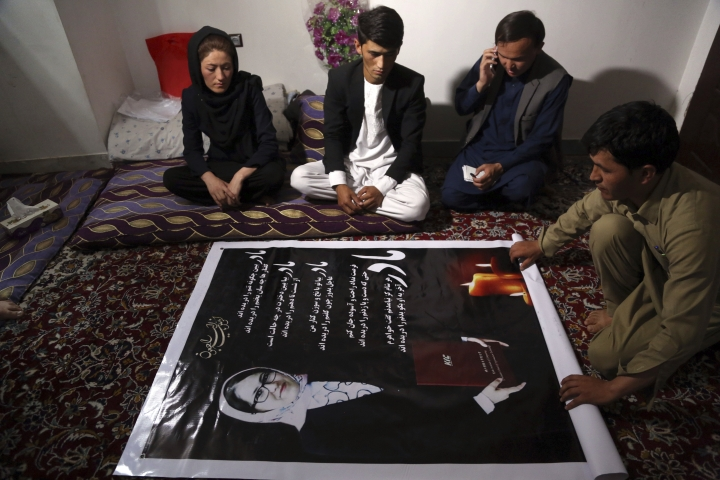 In this Thursday, Aug. 3, 2017 photo, Maryam Hossaini, left, whose sister Najiba was killed in a suicide attack last month, looks at a poster showing her sister during an interview with The Associated Press, in Kabul, Afghanistan. Najiba and Maryam, were part of the first generation of Afghan women to attend school after the fall of the Taliban, who had outlawed women's education. (AP Photo/Rahmat Gul)