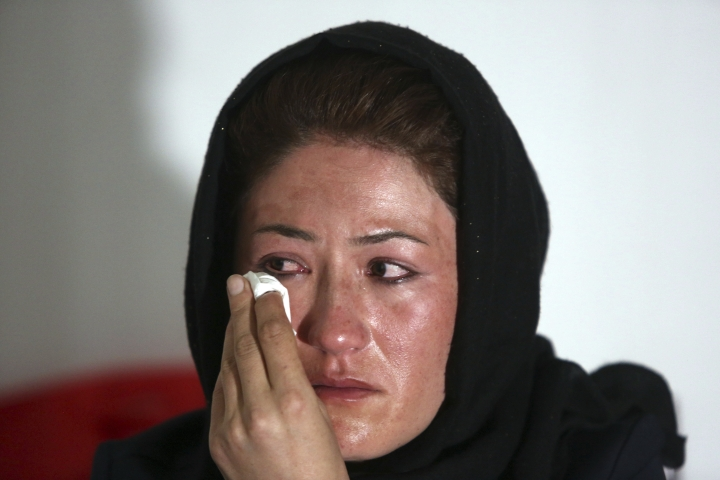In this Thursday, Aug. 3, 2017 photo, Maryam Hossaini, left, whose sister, Najiba, was killed in a suicide attack last month, wipes a tear during an interview with The Associated Press, in Kabul, Afghanistan. Najiba and Maryam, were part of the first generation of Afghan women to attend school after the fall of the Taliban, who had outlawed women's education. (AP Photo/Rahmat Gul)