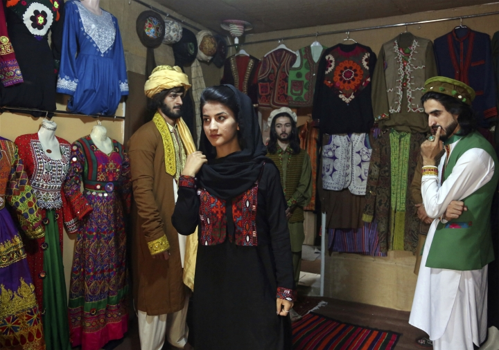 In this Thursday, Aug. 3, 2017 photo, Mahal Wak, center, a model for traditional embroidered Afghan clothing, practices modeling, in Kabul, Afghanistan. Her employer, Ajmal Haqiqi, who hails from the restive Ghazni province, said he exhibits and markets the traditional clothing in hopes of preserving Afghanistan's 5,000-year-old culture. (AP Photo/Rahmat Gul)