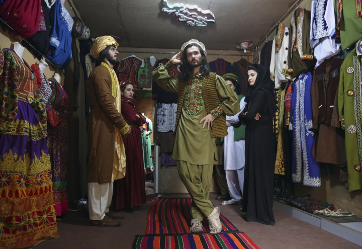 In this Thursday, Aug. 3, 2017 photo, Omid Arman, center, a model for traditional embroidered Afghan clothing, practices modeling, in Kabul, Afghanistan. His employer, Ajmal Haqiqi, who hails from the restive Ghazni province, said he exhibits and markets the traditional clothing in hopes of preserving Afghanistan's 5,000-year-old culture. (AP Photo/Rahmat Gul)