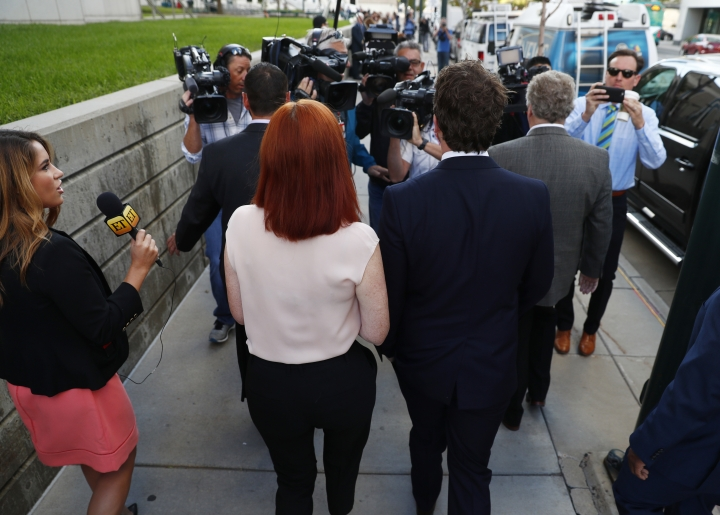 A brace of photographers back up as Tree Paine, front left, publicist for pop singer Taylor Swift, and Swift's brother, Austin, head into the federal courthouse for day six in the civil trial involving the pop singer Monday, Aug. 14, 2017, in Denver. While the judge has cleared the pop singer, her mother, Andrea, and the singer's radio liaison are still facing allegations that they set out to have a radio host fired for allegedly groping Swift at a photo op before a concert in Denver in 2013. The eight-person jury is expected to decide on that case as well as consider the assault allegation leveled by the singer. (AP Photo/David Zalubowski)
