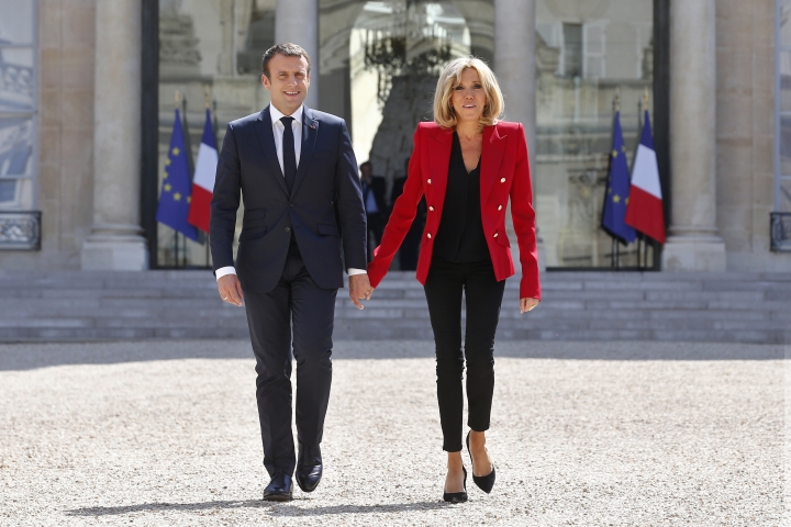 """FILE- In this Thursday, July 6, 2017 file photo, France's President Emmanuel Macron and his wife Brigitte, walk toward the Elysee Palace courtyard, to welcome autistic people, prior to the launching of a program to enhance the diagnosis and treatment of autism, in Paris. The French president's wife says Emmanuel Macron's only fault is """"being younger than me,"""" addressing their unusual love story in a rare interview released Wednesday, Aug. 16, 2017. (AP Photo/Thibault Camus, Pool, File)"""