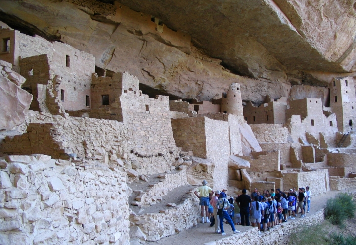FILE - In this Aug. 27, 2005 file photo, visitors tour Cliff Palace, an ancient cliff dwelling in Mesa Verde National Park, Colo. Researchers say they have new evidence that ancestral Pueblo people who disappeared from the Mesa Verde cliff dwellings of southwestern Colorado 700 years ago migrated to what is now New Mexico. DNA from the bones of domesticated turkeys. The turkey DNA shows Native American people in the Rio Grande Valley of northern New Mexico raised and ate the same genetic strain of bird as the Mesa Verde people, and that the turkeys arrived in New Mexico about the same time Mesa Verde was abandoned, the researchers said. (AP Photo/Beth J. Harpaz,File)