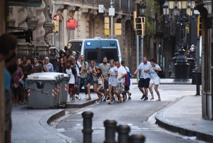 People flee from the scene after a white van jumped the sidewalk in the historic Las Ramblas district of Barcelona, Spain, crashing into a summer crowd of residents and tourists Thursday, Aug. 17, 2017. According to witnesses the white van swerved from side to side as it plowed into tourists and residents. (AP Photo/Giannis Papanikos)