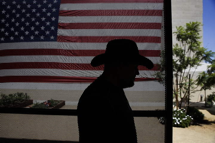 In this Monday, Aug. 14, 2017 photo, Iraq war veteran Vernon Poling, 44, walks through a courtyard past a giant American flag at Potter's Lane, an apartment complex made out of shipping containers in Midway City, Calif. Poling was the last of 15 homeless veterans to move into the $6.7 million project paid for with federal, state, and local dollars, donations, and among other sources, the nonprofit behind the project, American Family Housing. (AP Photo/Jae C. Hong)