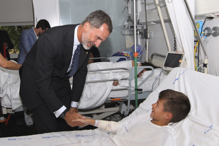 EDS NOTE : SPANISH LAW REQUIRES THAT THE FACES OF MINORS ARE MASKED IN PUBLICATIONS WITHIN SPAIN. Spain's King Felipe speaks to one of the victims of the van attacks at a hospital in Barcelona , Spain, Saturday, Aug. 19, 2017. Police on Friday shot and killed five people carrying bomb belts who were connected to the Barcelona van attack, as the manhunt intensified for the perpetrators of Europe's latest rampage claimed by the Islamic State group. (Spanish Royal Palace, Pool Photo via AP)