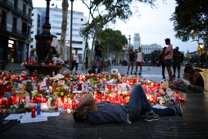A man lays down next to messages and candles placed after a van attack that killed at least 13, in central Barcelona, Spain, Saturday, Aug. 19, 2017. Police on Friday shot and killed five people carrying bomb belts who were connected to the Barcelona van attack, as the manhunt intensified for the perpetrators of Europe's latest rampage claimed by the Islamic State group. (AP Photo/Manu Fernandez)