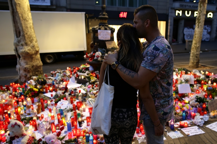A couple looks at flags, messages and candles placed after van attack that killed at least 13, in central Barcelona, Spain, Saturday, Aug. 19, 2017. Police on Friday shot and killed five people carrying bomb belts who were connected to the Barcelona van attack, as the manhunt intensified for the perpetrators of Europe's latest rampage claimed by the Islamic State group. (AP Photo/Manu Fernandez)